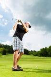 Jogador de golfe novo no curso que faz o balanço do golfe Fotos de Stock Royalty Free
