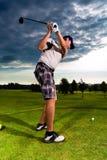 Jogador de golfe novo no curso que faz o balanço do golfe imagem de stock