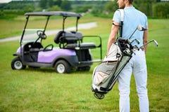 Jogador de golfe que anda com sacos de golfe fotografia de stock