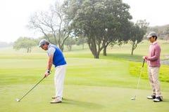 Jogador de golfe que balança seu clube com o amigo atrás dele Foto de Stock