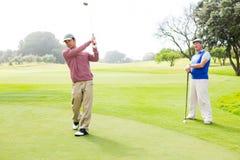 Jogador de golfe que balança seu clube com o amigo atrás dele Fotografia de Stock Royalty Free