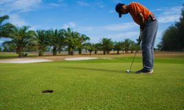 Jogador de golfe que bate o tiro de golfe com o clube no tom da cor do vintage do curso, homem que joga o golfe em um campo de go imagens de stock royalty free