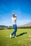 Jogador de golfe que joga um tiro no fairway Imagens de Stock Royalty Free