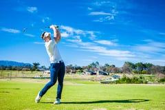 Jogador de golfe que joga um tiro no fairway Fotografia de Stock