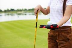 Jogador de golfe que mostra o clube de golfe da terra arrendada da esfera de golfe Imagem de Stock Royalty Free