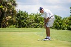 Jogador de golfe que põe a bola sobre o verde imagens de stock royalty free