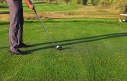 Jogador de golfe que põe, foco seletivo na bola de golfe Fotografia de Stock Royalty Free