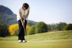 Jogador de golfe que põr a esfera. Imagens de Stock