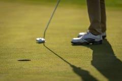 Jogador de golfe que põr sobre o verde Imagens de Stock