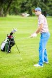 Jogador de golfe que pratica e que concentra-se antes e depois do tiro fotos de stock