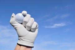 Jogador de golfe que prende uma esfera de golfe Fotografia de Stock Royalty Free
