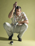 Jogador de golfe que Squatting com clube e bola Fotos de Stock
