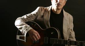 Jogador de guitarra do jazz que joga o instrumento fotografia de stock