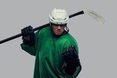 Jogador de hóquei profissional irritado no sportswear verde que está com uma vara de hóquei em um fundo cinzento imagem de stock