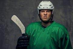 Jogador de hóquei profissional irritado no sportswear verde que está com uma vara de hóquei em um fundo cinzento imagens de stock