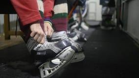 Jogador de hóquei que amarram o laço na patinagem e pronto para ir na pista, fundo unfocused filme