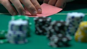 Jogador de pôquer arriscado que verifica seus cartões e que levanta a aposta, blefe corajoso, jogando vídeos de arquivo