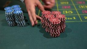 Jogador de pôquer do negociante com as microplaquetas na tabela do casino vídeos de arquivo
