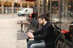 Jogador de pôquer em linha que usa a tabuleta na tabela do café dentro fotos de stock