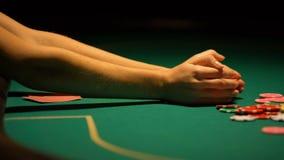 Jogador de pôquer que aposta microplaquetas e chaves para abrigar, indo apego tudo, jogando video estoque