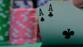 Jogador de pôquer que mostra a boa combinação do cartão, um par de áss no movimento lento video estoque