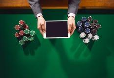 Jogador de pôquer com tabuleta digital imagens de stock royalty free