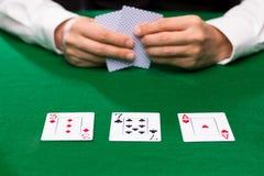 Jogador de pôquer que guarda cartões de jogo na tabela do casino Fotografia de Stock Royalty Free