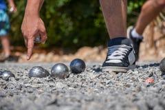 Jogador de Petanque que aponta na terra, guardando uma bola de aço Foto de Stock