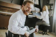 Jogador de piano novo acompanhado de um guitarrista masculino foto de stock