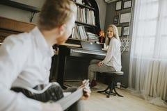 Jogador de piano novo acompanhado de um guitarrista masculino fotografia de stock
