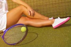 Jogador de tênis bonito da menina que senta-se no kort do treinamento Fotos de Stock
