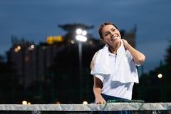 Jogador de tênis da mulher com ferimento que guarda a raquete em um campo de tênis foto de stock royalty free