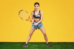 Jogador de tênis desportivo considerável da jovem mulher pronto ao tiro a bola com a raquete vermelha sobre o fundo amarelo imagens de stock