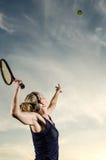Jogador de tênis fêmea aproximadamente para servir a bola Imagens de Stock Royalty Free