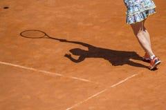 Jogador de tênis fêmea na ação na corte em um dia ensolarado imagens de stock royalty free