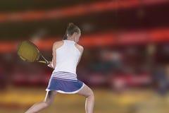 Jogador de tênis fêmea que alcança para bater a bola de tênis na corte imagens de stock