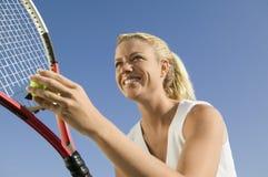 Jogador de tênis fêmea que prepara-se para servir acima o fim da opinião de baixo ângulo Imagem de Stock