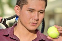Jogador de tênis masculino filipino sério com raquete de tênis imagens de stock