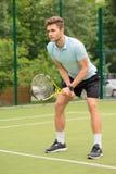 Jogador de tênis novo hábil pronto para bater a bola Fotografia de Stock Royalty Free