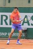Jogador de tênis profissional Bernard Tomic de Austrália na ação o seu durante o primeiro fósforo do círculo em Roland Garros Fotos de Stock Royalty Free
