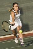 Jogador de tênis que alcança para bater a bola fotografia de stock