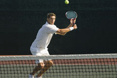 Jogador de tênis que bate revés na corte Foto de Stock Royalty Free
