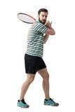 Jogador de tênis que espera para bater a bola que guarda a raquete com ambas as mãos na pose dos revés Imagens de Stock Royalty Free