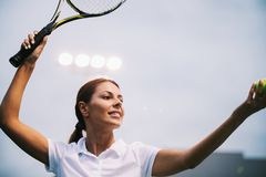 Jogador de t?nis da mulher que sorri ao guardar a raquete durante o f?sforo do t?nis fotos de stock royalty free