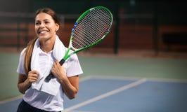 Jogador de t?nis da mulher que sorri ao guardar a raquete durante o f?sforo do t?nis fotografia de stock royalty free