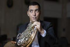 Jogador de trompa francesa Hornist que joga o instrumento de música de bronze da orquestra fotos de stock royalty free