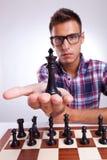 Jogador de xadrez do homem novo que sustenta seu rei Foto de Stock