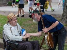 Jogador do banjo com o homem na cadeira de rodas no estado de Iowa justo foto de stock royalty free