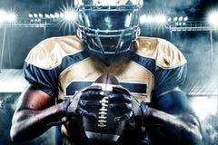 Jogador do desportista do futebol americano no estádio com luzes no fundo Fotos de Stock Royalty Free