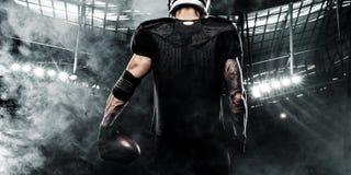 Jogador do desportista do futebol americano no estádio Bandeira e papel de parede dos esportes com copyspace imagem de stock